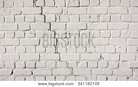 White Brick Wall. Light Background Of Cracked Masonry. Old Texture Stained Blocks Of Stonework.