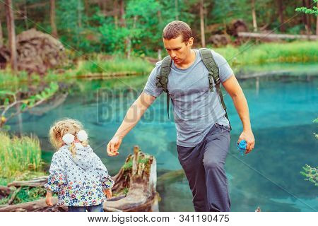 Dad With A Child In The Woods During A Hike Near The Lake