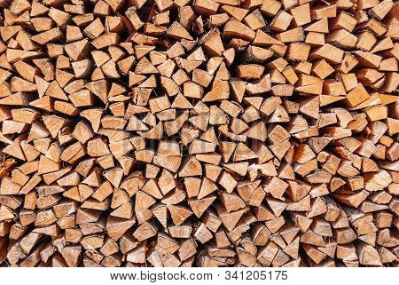 Dry Chopped Wood Stacked In A Woodpile, As A Background
