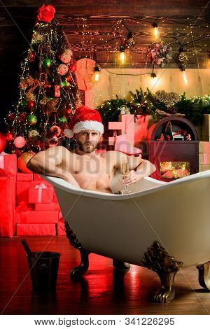 Hedonism Concept. Man Celebrate New Year Lying In Bathtub With Glass Of Sparkling Wine. Luxury Life.