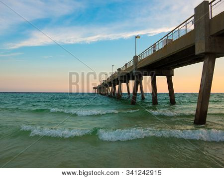 Pensacola Beach With Turquoise Waters, Waves And Pier Entering Into Gulf Of Mexico. Clouds Visible,