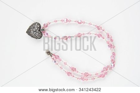 Pink Swarovski Beaded Jewelry Necklace With A Heart Shaped Embellishment, Isolated On A Light Backgr