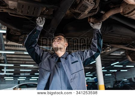 Smiling Mechanic Inspecting Bottom Of Raised Car With Wrench