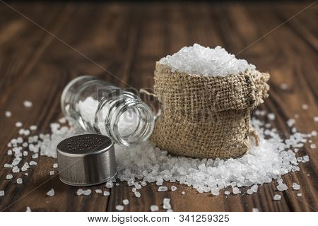 A Bag Of Scattered Salt And A Glass Salt Shaker On A Wooden Table. Ground Stone Sea Salt.