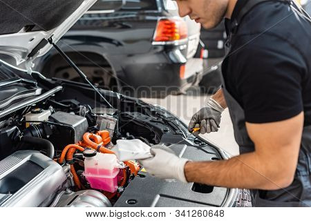 Partial View Of Mechanic Wiping Oil Dipstick With Rag Near Car Engine Compartment