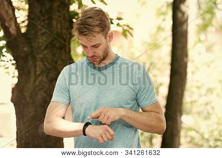 Tracking His Training With A Sports Watch. Handsome Athlete Using Smart Watch During Training Outdoo