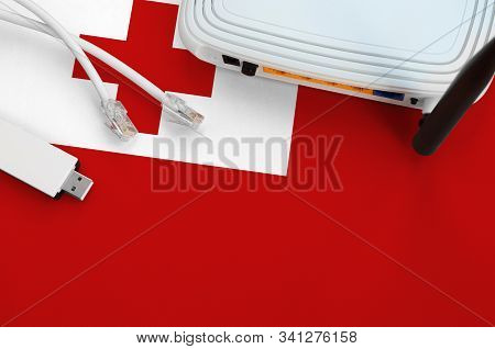 Tonga Flag Depicted On Table With Internet Rj45 Cable, Wireless Usb Wifi Adapter And Router. Interne