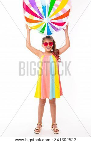 Photo In Full Growth, A Surprised Girl In Sunglasses Holds An Inflatable Colored Striped Ball Over A