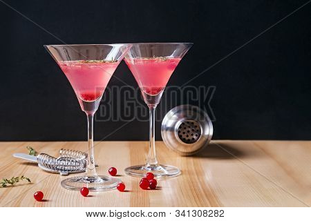 Two Martini Glasses Filled With Red Color Cranberry Cocktail And Barmen Tools On The Wooden Table