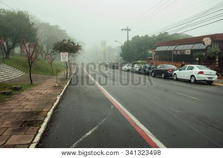 Bento Goncalves, Brazil - July 14, 2019. Quiet Paved Street With Houses And Parked Cars, On A Foggy