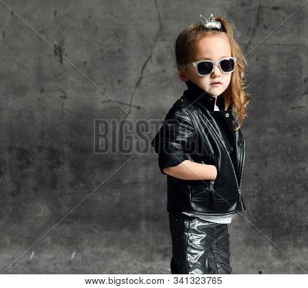 Cool Brutal Kid Girl With A Crown Pin In Her Hair And In Leather Jacket, Jeans And Sunglasses Is Pos