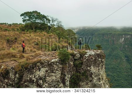 Cambara Do Sul, Brazil, July 17, 2019. People On Steep Rocky Cliff In Fortaleza Canyon With Fog Comi