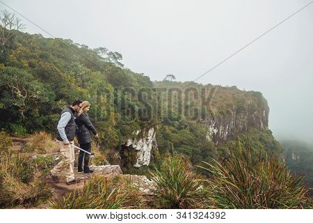 Cambara Do Sul - Brazil, July 18, 2019. People On The Edge Of Rocky Cliff And Mist At Serra Geral Na