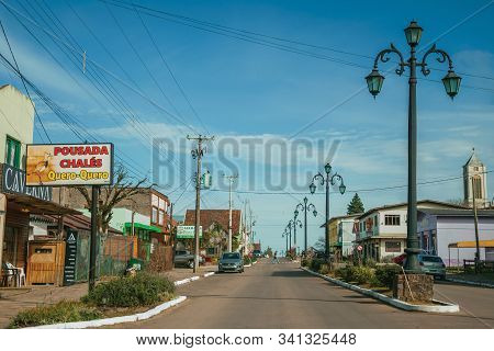 Cambara Do Sul, Brazil - July 19, 2019. Flamboyant Light Poles And Houses With Store On The Getulio