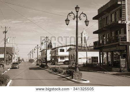 Cambara Do Sul, Brazil - July 19, 2019. Light Poles And Houses With Store On The Getulio Vargas Aven