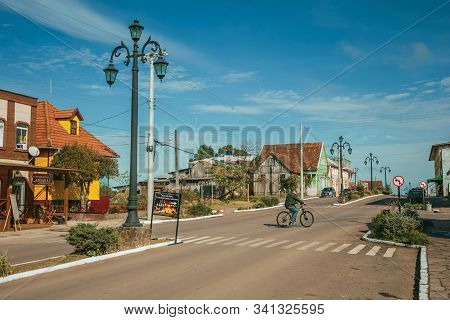 Cambara Do Sul, Brazil - July 19, 2019. Flamboyant Light Poles And Cyclist Pedaling On The Getulio V