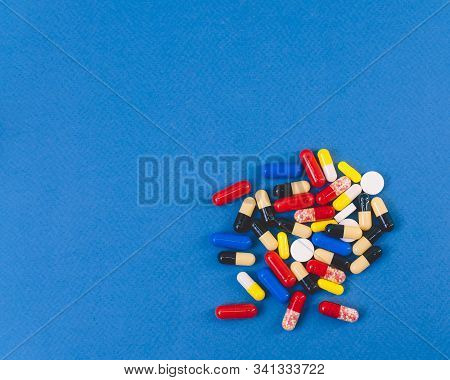 A Pile Of Colorful Pills And Capsules Lying In A Pile On A Blue Background