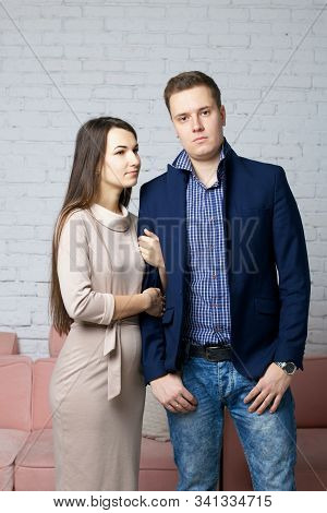 Husband And Wife On The Set In The Studio. The Wife With Tenderness Holds Her Husband's Arm. A Husba