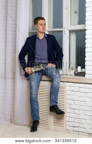 Young Man With An Arrogant Expression. Sits By The Window On The Windowsill. In His Hand Holds A Mag