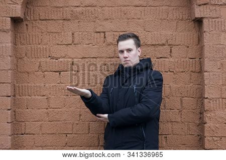 A Young Man In A Black Jacket Poses On A Background Of A Brown Brick Wall. He Took His Hand To The S