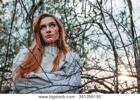 Girl With Long Hair In Straitjacket, Outside In The Woods, Branches Surrounding Her. Mental Breakdow