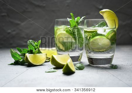 Refreshing Mojito Cocktail  With Mint, Rum And Lime, Cold Drink Or Beverage With Ice On Dark Stone T