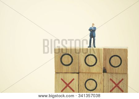Business Direction And Planning Concept. Businessman Miniature Standing And Thinking On O X Board Ga
