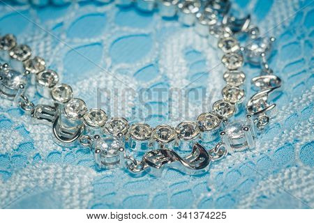 Fashion Silver Bracelet With White Cubic Zirconia On Blue Lace Background.