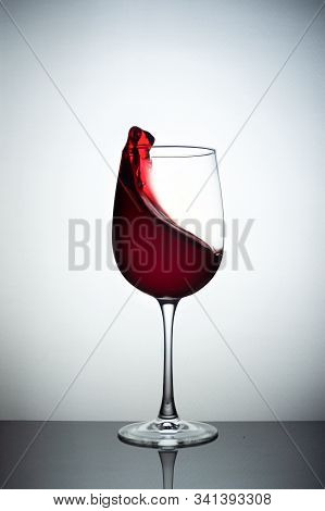 Creative Photo Of Wine Glass With Storm In A Glass On White Background. A Wine Glass Filled Wine And