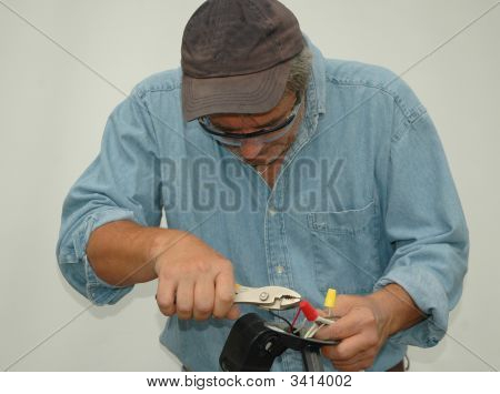 Older Blue Collar Worker Working On Electrical