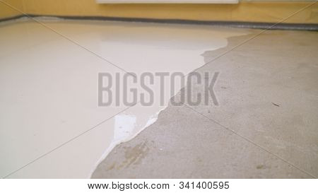 Interior Of Apartment Under Construction. Mirror Smooth Surface Of The Floor. Floor Covering With Se
