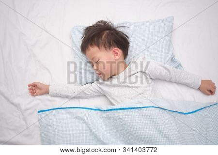 Cute Little Asian 3 - 4 Years Old Toddler Boy Kid In Pajama Taking A Nap, Sleeping On His Back  On W