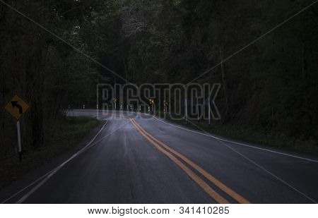 Road On The Dark View On The Mountain Road Among Green Forest Trees / Curve Asphalt Road Lonely Scar