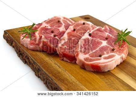 Raw Pork Steak On Wood Cutting Board. Pork With Spices: Rosemary And Pepper. Close-up Raw Pork Steak