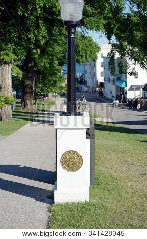 Mackinac Island, Michigan / United States - June 11, 2018:: A Plaque On The Base Of A Lamppost Bears