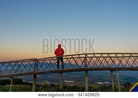 Silhouetted Of Asian Man Standing On Bamboo Bridge At Ban Doi Sa-ngo Chiangsaen, Chiang Rai Province