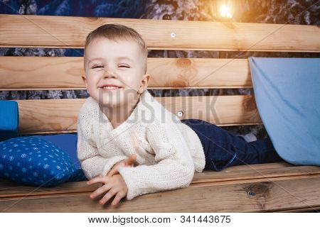 Small Cute Boy Laying On The Wooden Bench Holding A Blue Pillow With Snowflakes Indoor