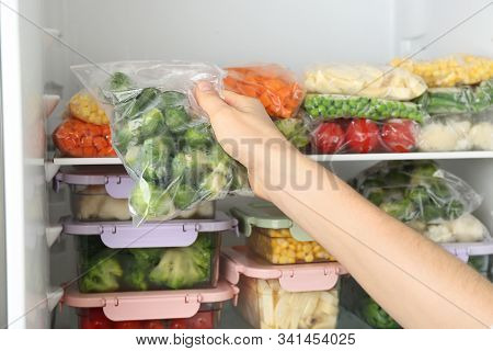 Woman Putting Plastic Bag With Brussels Sprouts In Refrigerator With Frozen Vegetables, Closeup