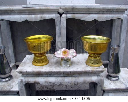 Two offering bowls (pyxes?) and a flower in front of a shrine. Picture taken in the grounds of the Summer Palace Bangpa-In Thailand. poster