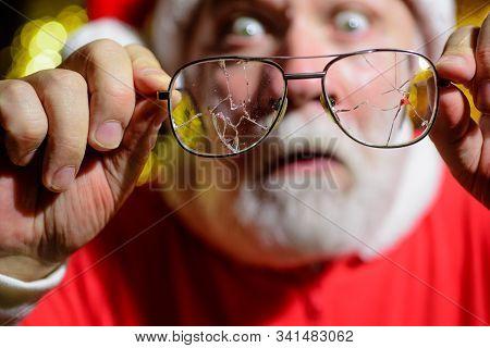 Santa Man With Broken Glasses. Selective Focus. Eyeglasses With Broken Lens. Santa Claus Holds Crack