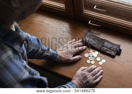 Hands Of An Old Man And Counting Money, Coins. The Concept Of Poverty, Low Income, Austerity In Old