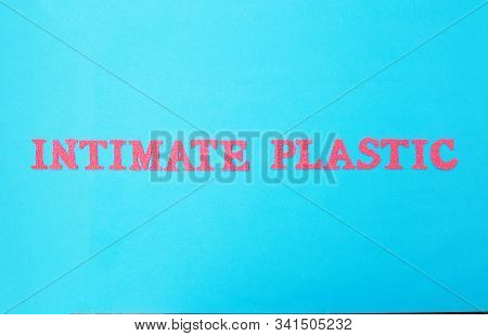 The Word Intimate Plastic In Red Letters On A Blue Background. The Concept Of Plastic Surgery Dealin