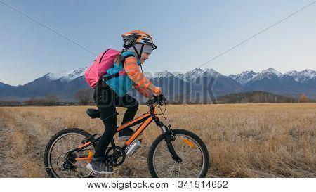 One Caucasian Children Rides Bike In Wheat Field. Little Girl Riding Black Orange Cycle On Backgroun