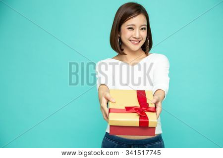 Happy Beautiful Asian Woman Smile With Gold Gift Box Isolated On Green Background. Teenage Girls In