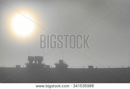 Sun Penetrating Through The Mist Over The Roof Of Apartment Building With Ventilation Chimneys