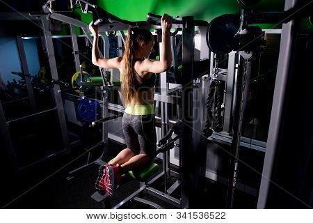 Girl Performs Pull-ups On A Gravitron, View From The Back