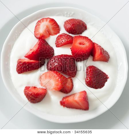 Porcelain bowl with strawberries and cream yogourt