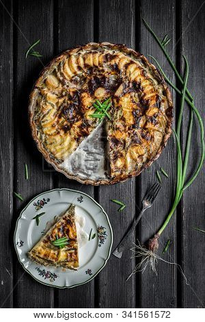 Potato And Spring Onion Gratin On A Rustic Table