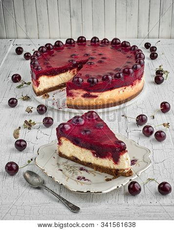 Sour Cherry And Orange Cheesecake On A White Rustic Board