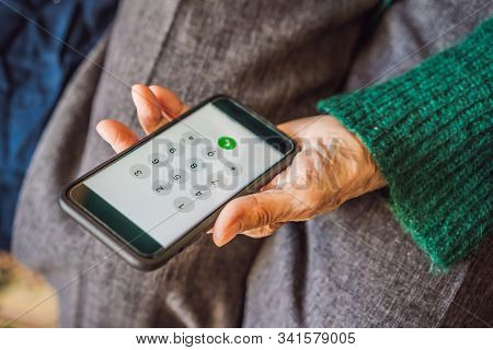Senior Woman Using Mobile Phone While Sitting On Sofa